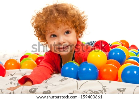 Close up of curly little girl lying down on colorful balls - stock photo
