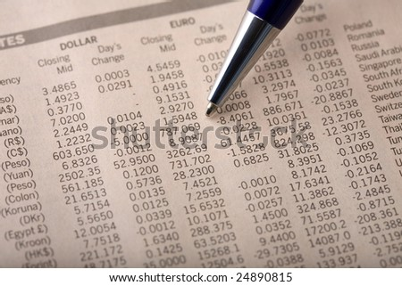 Close-up of currency exchange rate section of a financial newspaper, with pen pointing at forex rates - stock photo