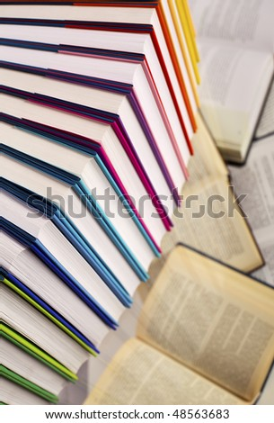Close-up of curve aligned in rainbow colors paper wrapped books with  open books below, top-down view, PHOTOGRAPH, NOT 3D RENDER. - stock photo