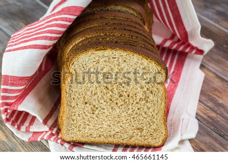 Close up of cut whole wheat bread on a wooden background.
