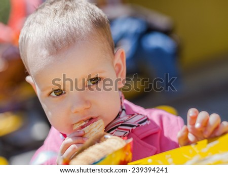 Close up of cute and happy two year girl Eating Cookie - stock photo