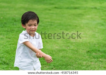 Close up of cute asian boy wear white shirt playing and happy in garden.