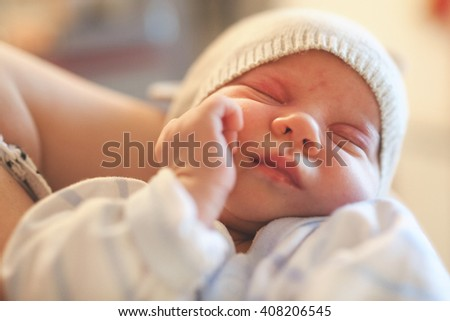 Close up of cute baby girl with hat sleeping in mom's hands. Post processed with sunny filter. - stock photo