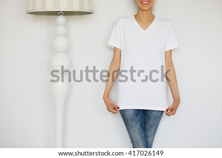 Close up of cute Caucasian teenage redhead girl in blank white T-shirt for your text message or advertising content. Cropped portrait of happy attractive young woman posing against white concrete wall - stock photo
