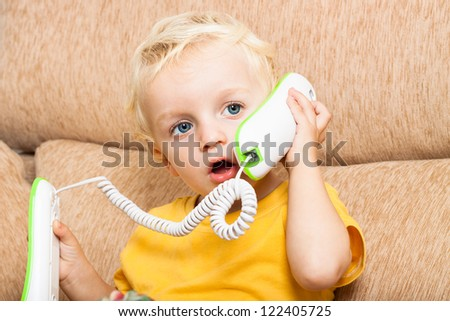 Close up of cute child boy using telephone. - stock photo