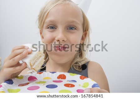 Close-up of cute girl eating birthday cake against gray background
