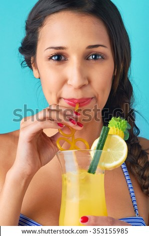 Close up of cute pretty girl drinking a cocktail, isolated on bright blue background
