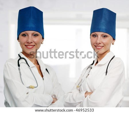 Close-up of cute sisters twins hospital staff. - stock photo