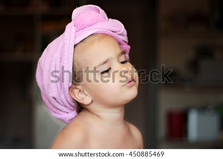 Close-up of cute small girl with pink bath towel on her head looking fondly and  romantic, beauty and health concept, indoor portrait - stock photo