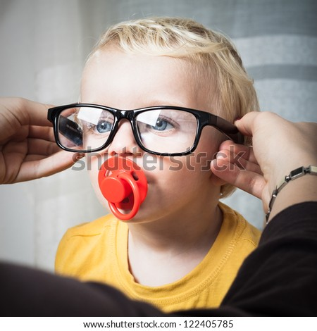 Close up of cute toddler child boy wearing eyeglasses.