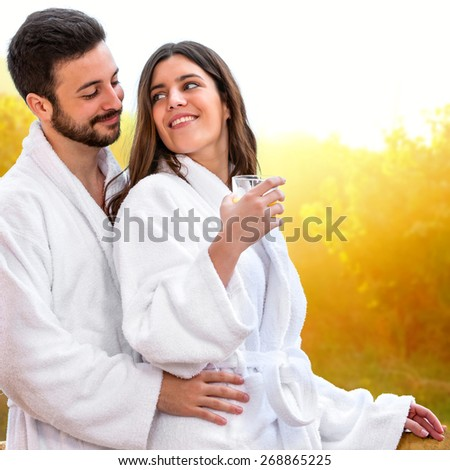 Close up of Cute young Couple in bathrobe ready for spa treatment. Couple standing on balcony against bright yellow rural background. - stock photo