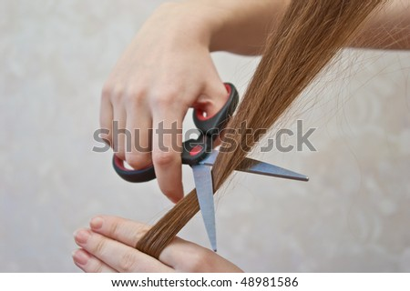 close-up of cutting lock of hair with scissors