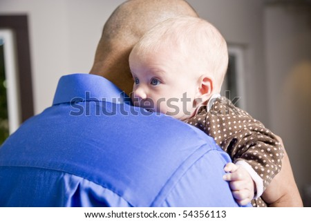 Close up of dad holding 3 month old baby on shoulder
