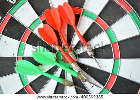 Close-up of darts arrows in the target center. Smart goal setting, dart hit the center of dartboard. Hit to the point. Business concept. -