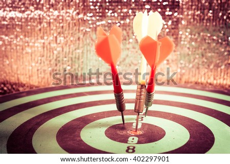 Close-up of darts arrows in the target center. Smart goal setting, dart hit the center of dartboard. Hit to the point. Business concept. - Vintage Tone - stock photo