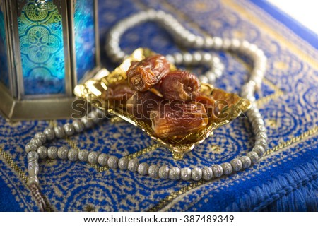 Close up of dates with islamic prayer beads near decorative Ramadan lamp. Religious objects. - stock photo