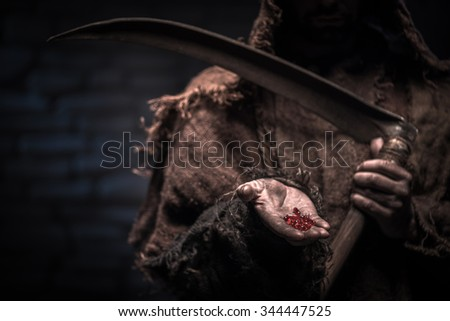 Close up of death character proposing red narcotic pills. He is standing and holding scythe in his left hand - stock photo