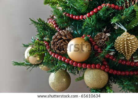 Close-up of decorated Christmas tree with cone, yellow ornaments and red berries