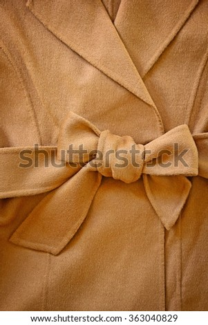 Close-up of decorative bowknot of wool waist belt with woolen coat. - stock photo