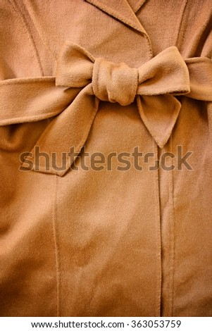 Close-up of decorative bowknot of woolen waist belt with wool coat. - stock photo