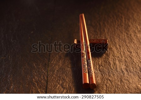Close Up of Decorative Chop Sticks Resting on Rest on Wooden Table Surface in Warm Mood Lighting with Copy Space