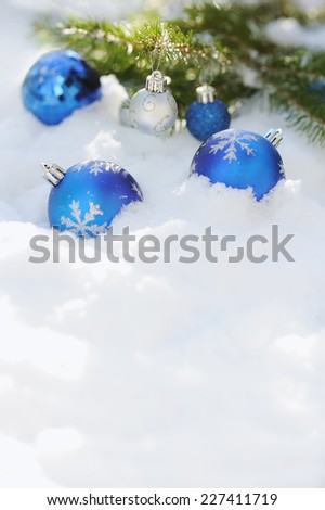Close up of decorative Cristmas balls on the snow and brunch of Cristmas tree outdoor - stock photo