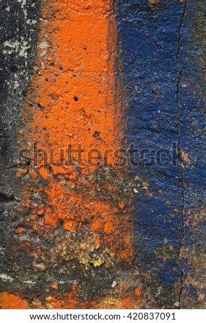 Close up of decorative  textured   mossed surface with  orange and blue   paintSolid,heavy, rough, material made from a mixture of broken stone or gravel, sand and cementAbstract grungy background  - stock photo