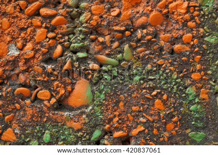 Close up of decorative  textured  mossed surface with orange and green  paintSolid,heavy, rough, material made from a mixture of broken stone or gravel, sand and cementAbstract grungy background  - stock photo