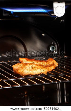 Close up of delicious golden chicken breast on gas grill
