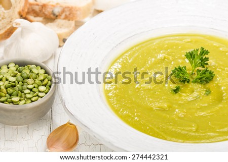Close up of delicious homemade split pea soup with garlic, bread and parsley for garnish. - stock photo