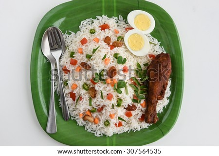 Close up of Delicious Indian Pulav / pilaf / fried rice,tomato flower on top in green plate with  Boiled egg, chicken drumsticks, spoon and fork. made of Basmati  rice, vegetable, nuts or meat,chicken - stock photo