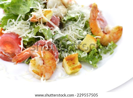 Close up of delicious salad with shrimps, croutons, vegetables and cheese served on white plate - stock photo
