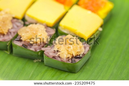 Close up of delicious Thai sticky rice with flavor on banana green leaf with white background  - stock photo