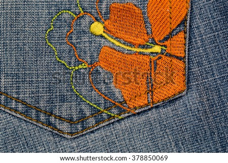 Close up of  denim jeans pocket with embroidered  flower - stock photo