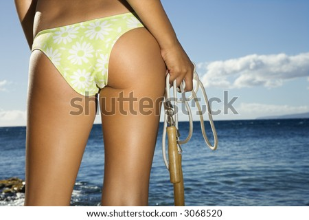 Close up of derriere of Asian Filipino young adult female holding jump rope in swimsuit on beach in Maui Hawaii. - stock photo