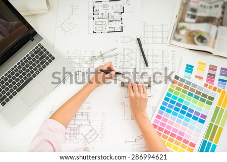 Close-up of designer's hands working with architectural plan with rule and pencil. - stock photo