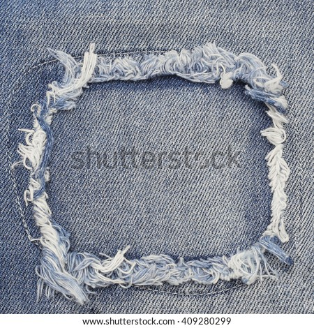 Close up of destroyed torn denim blue jeans patch  - stock photo