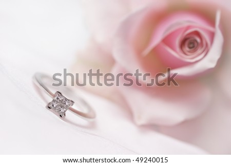 Close-up of diamond engagement ring with pink rose on background (shallow depth of field) - stock photo