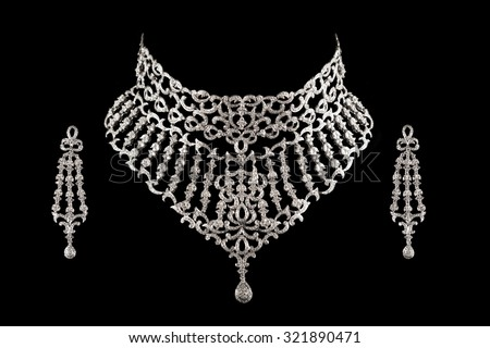 Close up of diamond necklace on black background with diamond earrings. - stock photo