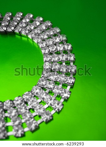 Close up of diamond necklace on green background - stock photo