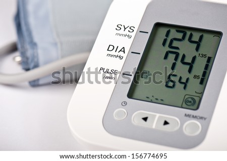 Close-up of digital blood pressure monitor with indicators of measurements on the screen