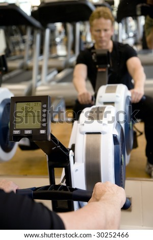 Close up of digital display on rowing machine in modern gym with reflection of personal trainer blurred in mirror. - stock photo