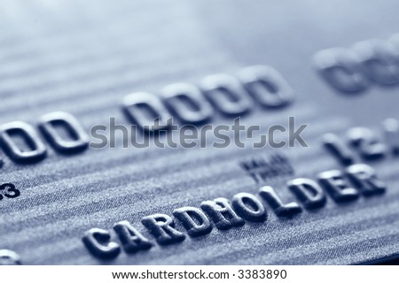 Close-up of digits on a credit card. Very shallow depth of field. Focus on letter D. Visible texture of the card. - stock photo