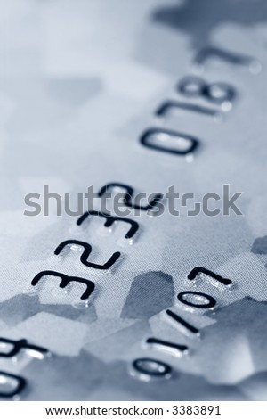 Close-up of digits on a credit card. Very shallow depth of field. Focus on numbers 3, 2 and 7. Visible texture of the card. - stock photo