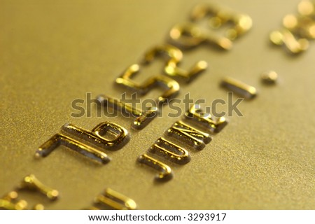 Close-up of digits on a gold credit card. Very shallow depth of field. Focus on number 6. Visible texture of the card. - stock photo