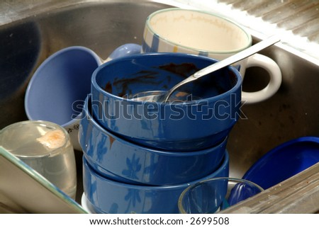 close up of dirty blue piled dishes,  cups and glasses in an aluminum sink