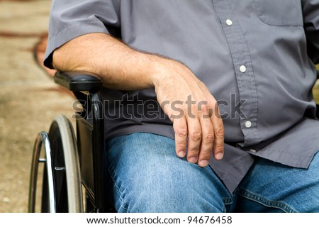 Close up of disabled man's arm and torso as he sits in a wheelchair. - stock photo