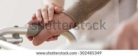 Close-up of disabled man walking with assistance - stock photo