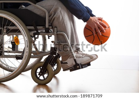 Close-up of disabled young man playing basketball - stock photo