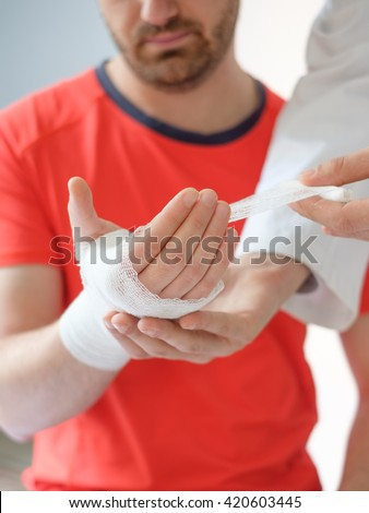 close up of doctor bandaging injured hand of a sport man after an accident - stock photo